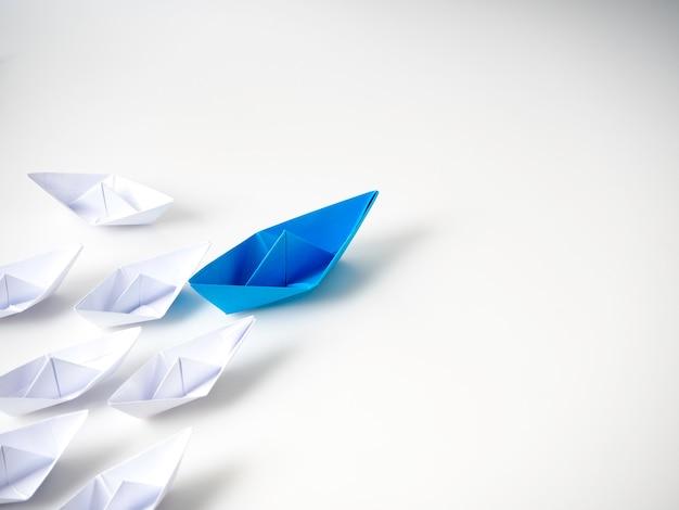 Barco de papel azul líder entre barcos blancos. Foto Premium