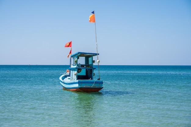 Barco de pescadores de madera con una bandera vietnamita Foto gratis