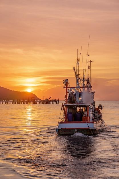 Barco de pescadores con poca luz flotando en el mar durante la puesta de sol dorada Foto Premium