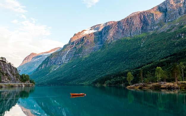 Barco rojo amarrado en el idílico lago cerca de las montañas rocosas Foto gratis