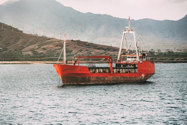 Barco viejo oxidado en el entrometido del mar Foto Premium