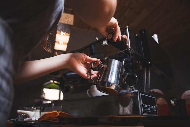 Barista femenina prepara café expreso de una máquina de café en la cafetería. Foto gratis