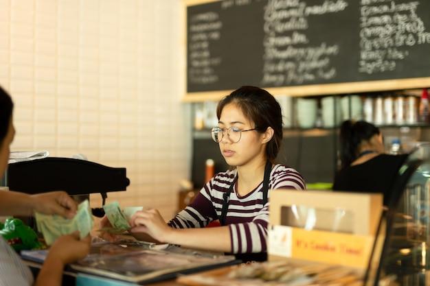 Barista joven que toma el dinero de la paga del cliente para la bebida en la cafetería. Foto Premium