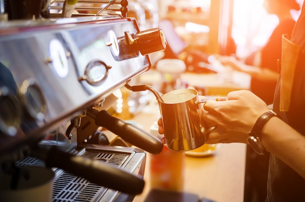 Barista masculino hacer café con leche arte en cafetería cafetería Foto Premium