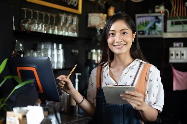 Barista de mujeres asiáticas sonriendo y usando máquina de café en mostrador de cafetería Foto Premium