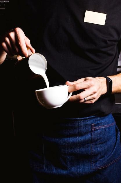 Barista prepara café con leche Foto gratis