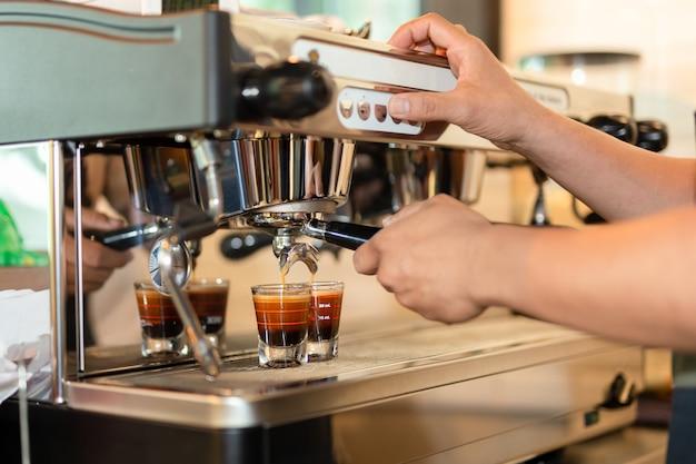 Barista preparando café espresso shot de máquina de preparar café. Foto Premium