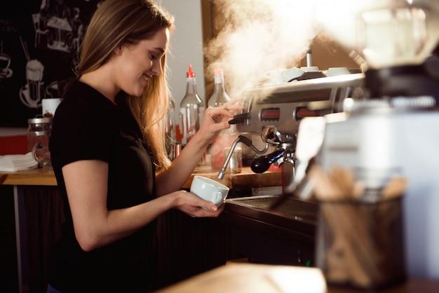 Barista de sexo femenino que hace el café en contador de la cafetería. mujer barista trabajando en cafe Foto Premium