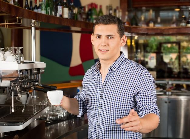 Barista sonriente hermoso que sostiene una taza de café y que señala el dedo. Foto Premium