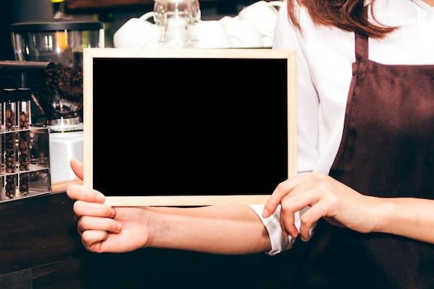 Barista sosteniendo la pizarra en el restaurante de la cafetería Foto Premium