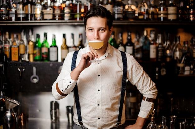 Barman en camisa blanca con cóctel en el stand del bar Foto Premium