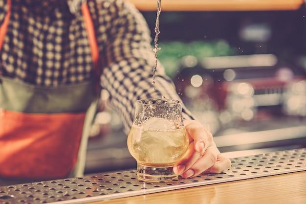 Barman haciendo un cóctel alcohólico en el mostrador del bar Foto gratis
