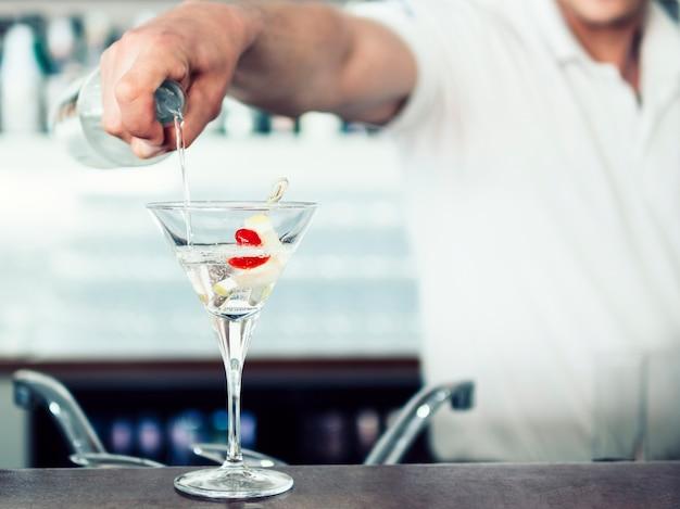 Barman irreconocible vertiendo cóctel en copa Foto gratis