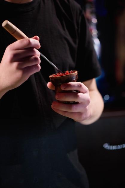 Barman llena un tazón de cerámica quemada negra para fumar narguile, diferentes tipos de tabaco. Foto Premium