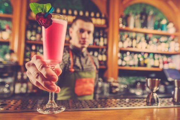 Barman ofreciendo un cóctel alcohólico en el mostrador del bar. Foto gratis