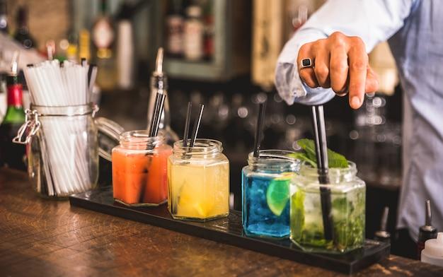 Barman profesional preparando cócteles en el bar de moda Foto Premium