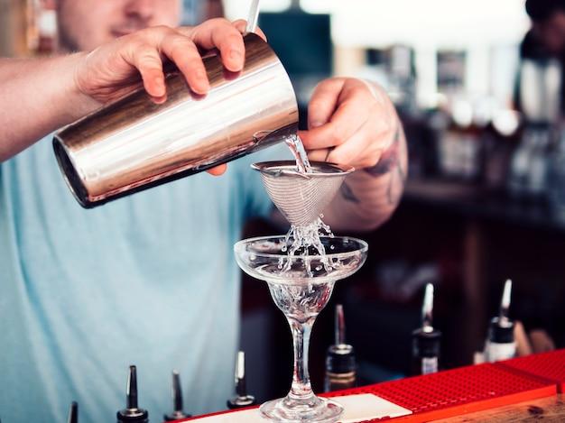 Barman relleno de copa de cóctel con bebida alcohólica Foto gratis
