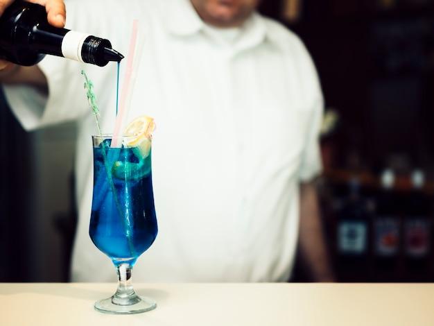 Barman relleno de vaso con bebida alcohólica azul Foto gratis