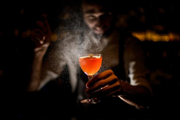 Barman sirviendo un cóctel con una rodaja de limón y una pequeña flor amarilla rociándola en la oscuridad Foto Premium