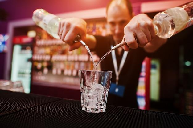 Barman sostenga la botella y sirviendo cócteles en el bar Foto Premium