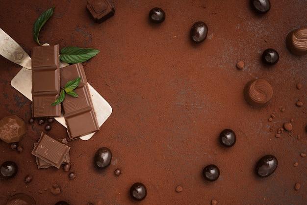 Barra de chocolate caramelos trufas y cacao en polvo con espacio de copia Foto gratis