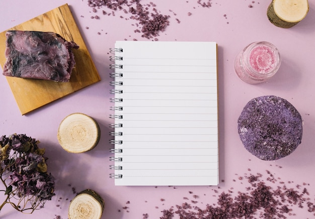 Barra de jabón de lavanda; tocón de madera; exfoliación corporal; flor seca y bloc de notas de una sola página sobre fondo rosa. Foto gratis