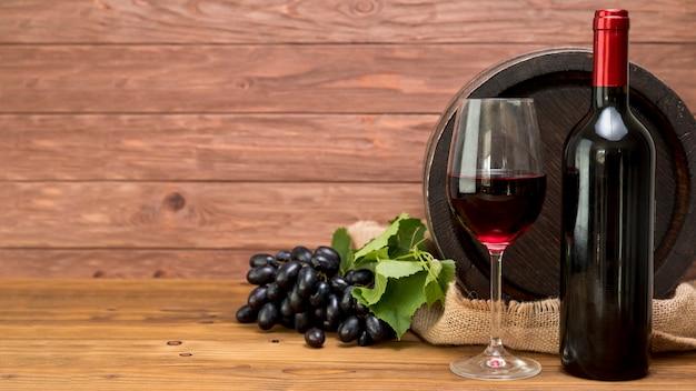 Barril de madera con botella y vaso de vino Foto gratis