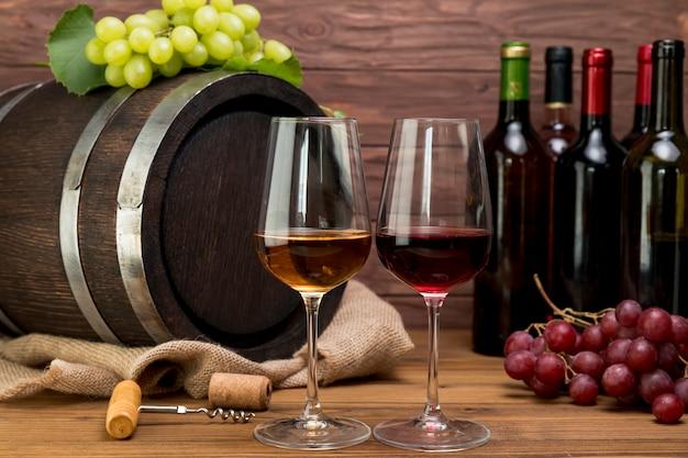 Barril de madera con botellas y vasos de vino Foto gratis