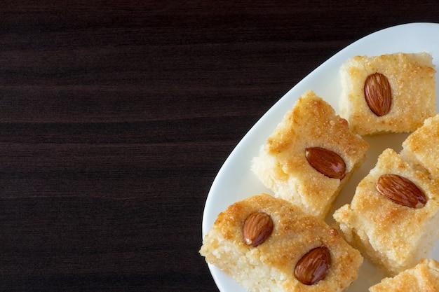 Basbousa (namoora) pastel de sémola árabe tradicional con almendras y jarabe. fondo oscuro Foto Premium