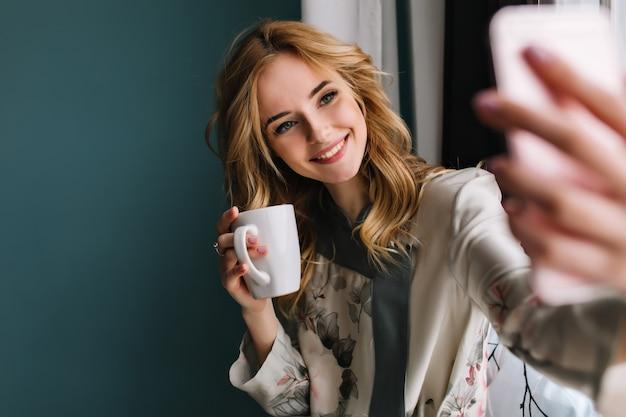 Bastante joven con cabello rubio ondulado tomando selfie sentado junto a la ventana con una taza de té, café por la mañana. lleva un pijama de seda. pared turquesa. Foto gratis