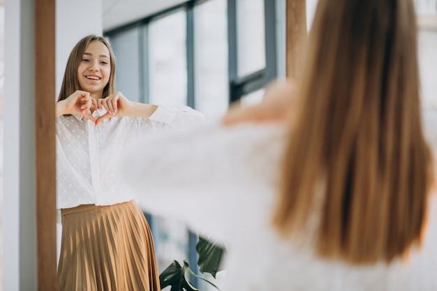 Bastante joven en ropa casual mirando en el espejo Foto gratis