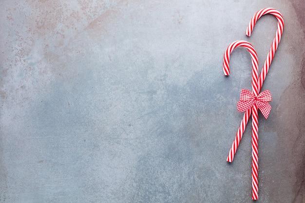 Bastón de caramelo de navidad mintió uniformemente en fila en azul Foto Premium