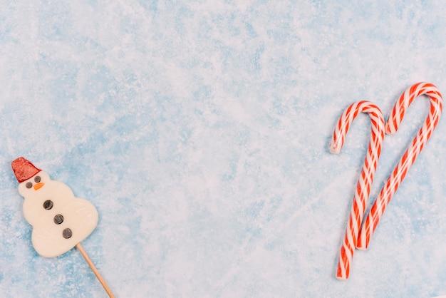 Bastones de caramelo y piruleta en forma de muñeco de nieve. Foto gratis