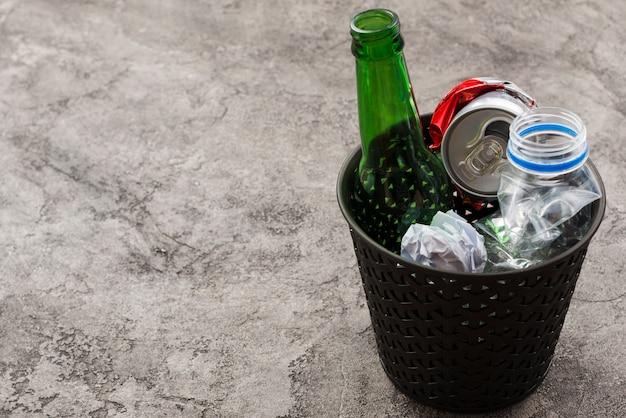 Basurero de basura con basura en superficie gris Foto gratis