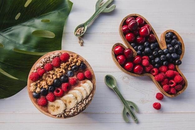 Batido de acai, granola, semillas, frutas frescas en un tazón de madera con una cuchara de cactus. plato relleno de bayas Foto Premium