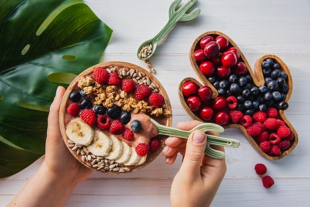 Batido de acai, granola, semillas, frutas frescas en un tazón de madera en manos femeninas con cuchara de cactus. plato relleno de bayas Foto Premium