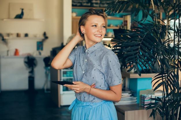 Batido de consumición de la mujer joven en el café, retrato feliz al aire libre Foto gratis