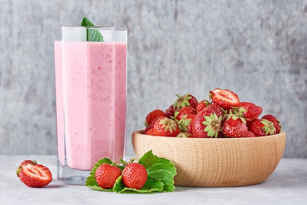 Batido de fresa en frasco de vidrio y fresas frescas en un tazón de madera en gris Foto Premium