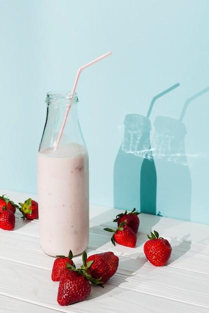 Batido de fresa rosa en botella de vidrio Foto gratis