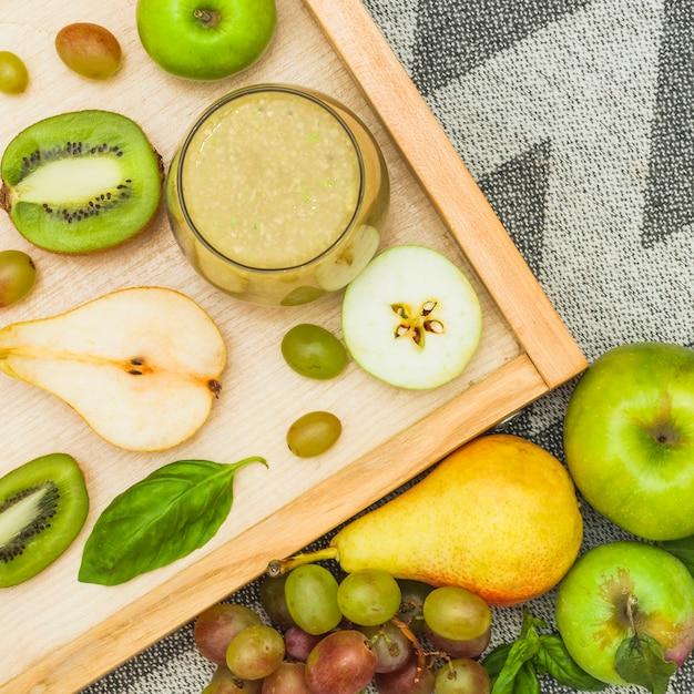 Batido de frutas y frutas frescas en bandeja de madera y sobre mantel Foto gratis