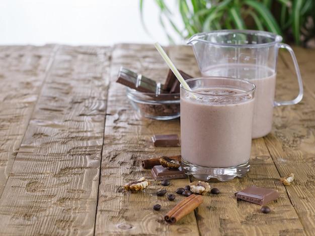 Batido de plátano con canela y chocolate en mesa rústica. Foto Premium