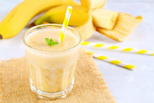 Batido de plátano con tubo de papel y menta. los plátanos son enteros y cortados sobre un fondo gris. Foto Premium
