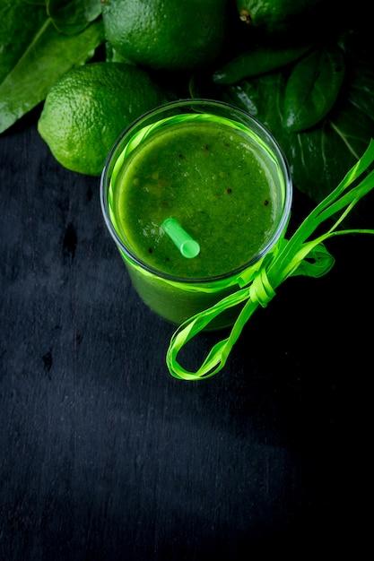 Batido verde e ingredientes para ello en madera negra. dieta. desintoxicación bebida saludable. vista superior Foto Premium