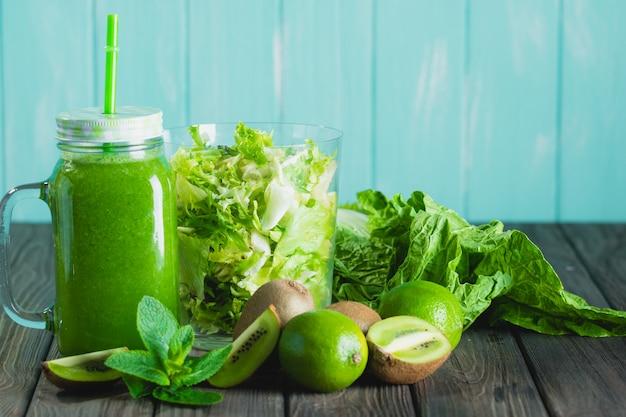 Batido verde mezclado con ingredientes en la mesa de madera Foto Premium