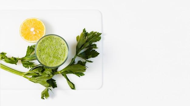 Batido verde plano en vaso con limón Foto gratis