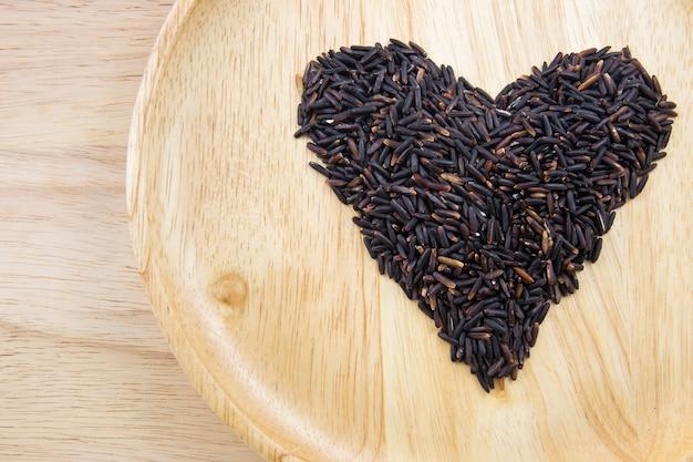 Baya del arroz del corazón en cuencos de madera en fondo de madera. concepto Foto Premium