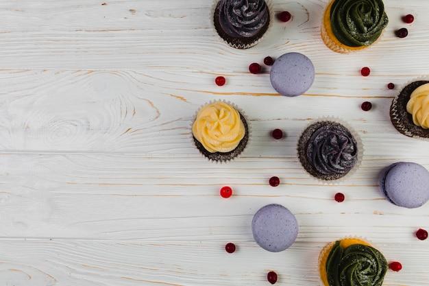 Bayas cerca de macarrones y muffins Foto gratis
