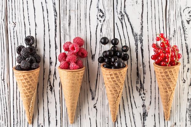 Bayas de verano en cono de waffle sobre fondo blanco de madera Foto Premium