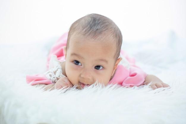 El bebé está acostado en una cama blanca. Foto gratis