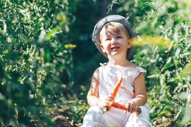 Bebé agricultor con zanahorias y ropa cacual sentado en la hierba verde Foto Premium